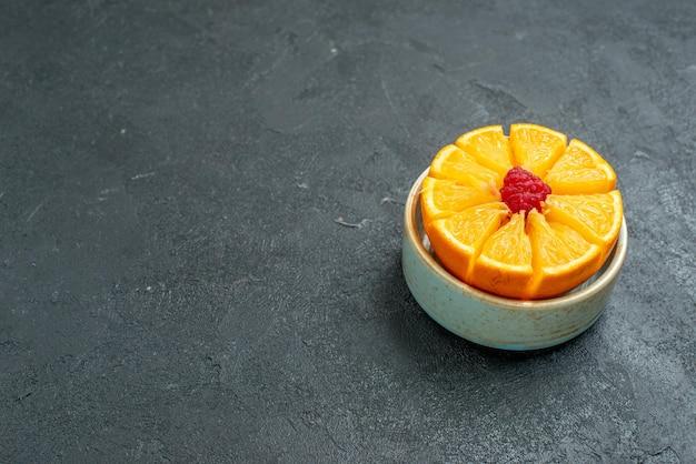 Widok z przodu pokrojone świeże pomarańcze wewnątrz talerza na ciemnym tle sok ze świeżych owoców cytrusowych