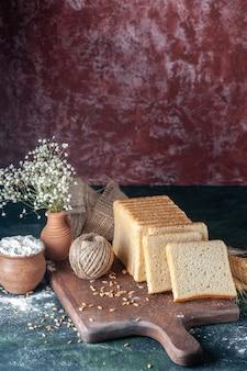 Widok z przodu pokrojony chleb na ciemnoniebieskim tle ciasto bułkowe piekarnia herbata rano bochenek ciasta jedzenie