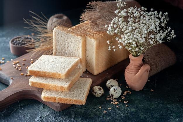 Widok z przodu pokrojony chleb na ciemnoniebieskim tle ciasto bułkowe piekarnia herbata rano bochenek jedzenie śniadanie