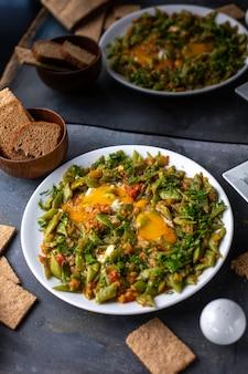 Widok z przodu pokrojony posiłek warzywny kolorowy smaczny wewnątrz białego talerza wraz z jajkami chrupiącymi na szarych warzywach stołowych