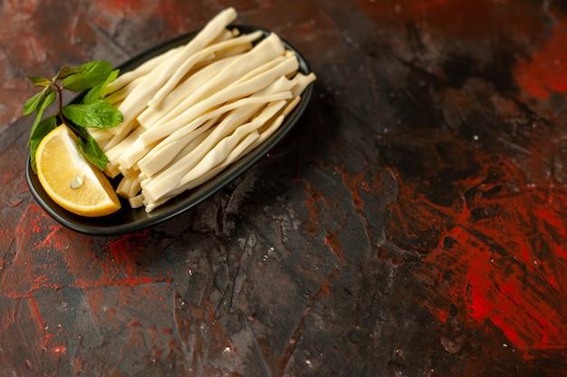 Widok z przodu pokrojony ser z kawałkiem cytryny wewnątrz talerza na ciemnym posiłku przekąska jedzenie kolor owoców zdjęcie wolne miejsce