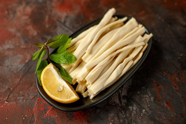 Widok z przodu pokrojony ser z kawałkiem cytryny wewnątrz talerza na ciemnym posiłku przekąska jedzenie kolor owoców zdjęcie