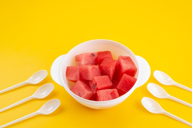 Widok z przodu pokrojony świeży arbuz wewnątrz białego plastikowego talerza na żółtym biurku
