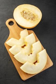 Widok z przodu pokrojony świeży melon łagodny, soczysty i słodki, wyłożony na drewnianym biurku i ciemny