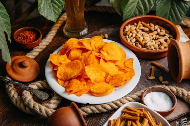 Widok z przodu pomarańczowe chipsy z orzeszkami ziemnymi i solą na drewnianym stole przekąska chipsy sól przyprawa