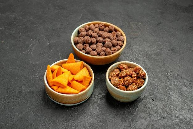 Widok z przodu pomarańczowe cipsy ze słodkimi orzechami i płatkami na szarym tle przekąska posiłek śniadanie orzech