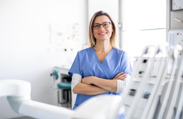 Widok z przodu portret asystentki dentystycznej w nowoczesnej chirurgii stomatologicznej, patrząc na kamery.