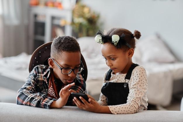 Widok z przodu portret dwóch afrykańskich dzieci używających smartfona razem w przytulnym wnętrzu domu...