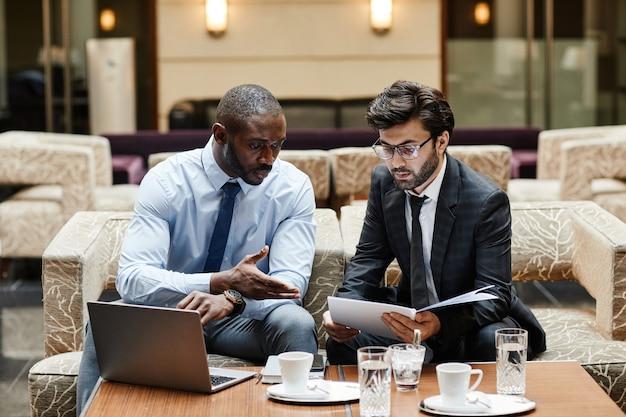 Widok z przodu portret dwóch ludzi biznesu omawiających pracę podczas spotkania w holu luksusowego hotelu, miejsce kopiowania