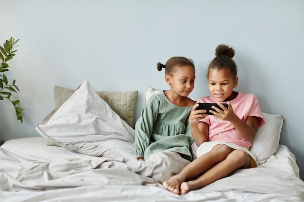 Widok z przodu portret dwóch uroczych afroamerykanek używających smartfona razem siedząc na łóżku...