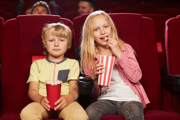Widok z przodu portret dwóch uroczych dzieci oglądających film w kinie i jedzących popcorn, miejsce na kopię