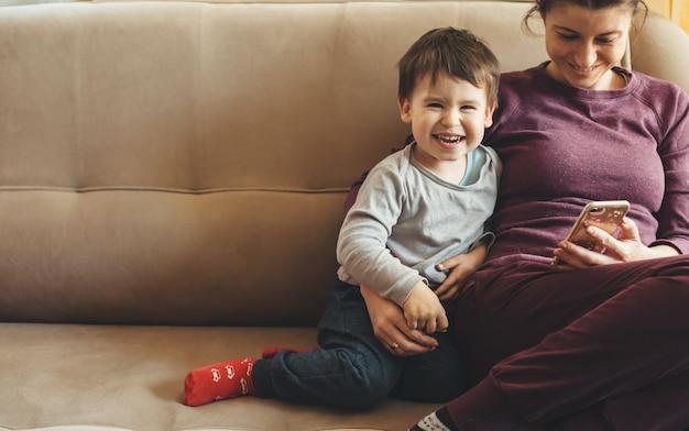 Widok z przodu portret kaukaskiej matki i syna siedzących na kanapie i przy użyciu telefonu komórkowego, uśmiechając się