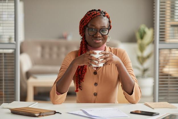 Widok z przodu portret młodej kobiety african-american gospodarstwa kubek kawy i uśmiecha się do kamery, ciesząc się pracą w domowym biurze, kopia przestrzeń