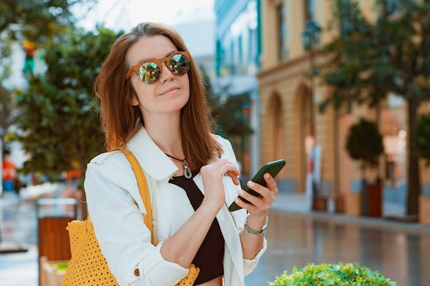 Widok z przodu portret nowoczesna moda szczęśliwa kobieta hipster chodząca i używająca smartfona na ulicy miasta...