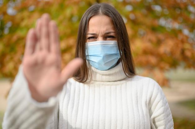 Widok z przodu portret poważnej dziewczyny wykonującej gest stopu z maską ochronną na ulicy miasta