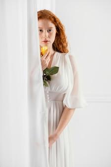 Widok z przodu powabnej kobiety pozuje z kwiatem wiosny