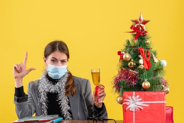 Widok z przodu poważna dziewczyna z maską medyczną siedzi przy stole opiekania choinki i koktajl prezentów