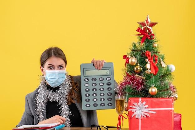 Widok z przodu poważna dziewczyna z maską medyczną siedzi przy stole trzymając kalkulator choinkę i koktajl prezentów