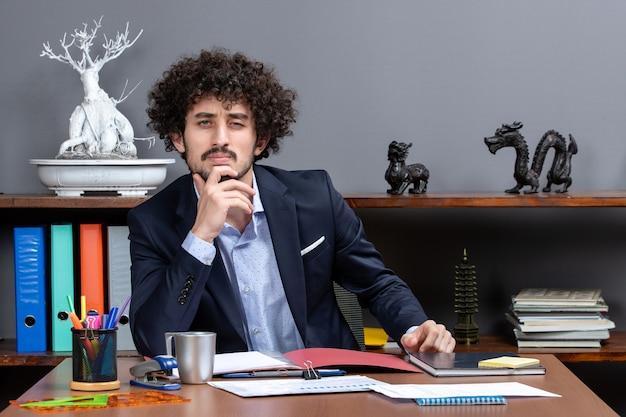 Widok z przodu poważnego biznesmena siedzącego przy biurku w biurze