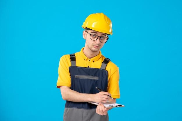 Widok z przodu poważnego konstruktora w mundurze robienia notatek na niebiesko