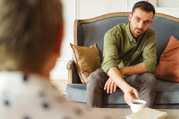 Widok z przodu poważnego przystojnego pacjenta płci męskiej siedzącego przed swoją kobietą psychoanalitykiem