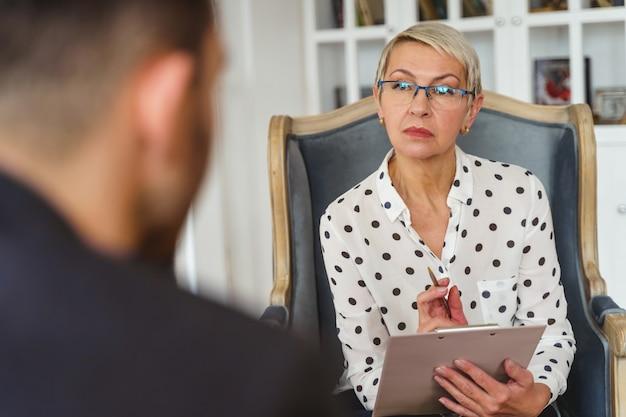 Widok Z Przodu Poważnej Psycholog W Okularach Siedzącej Przed Pacjentem Premium Zdjęcia