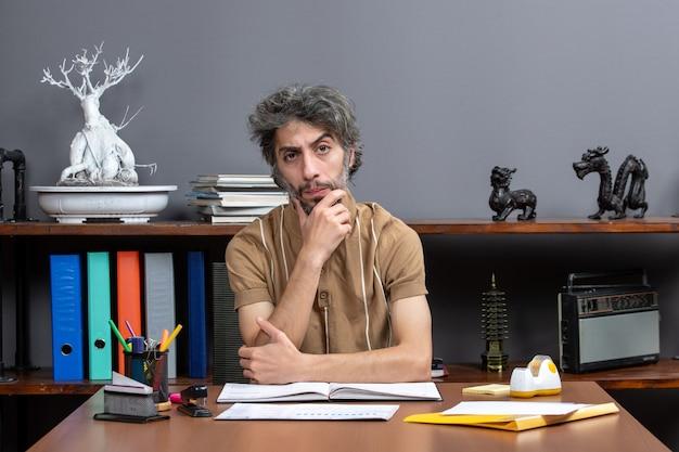 Widok z przodu poważny pracownik biurowy siedzący przy stole