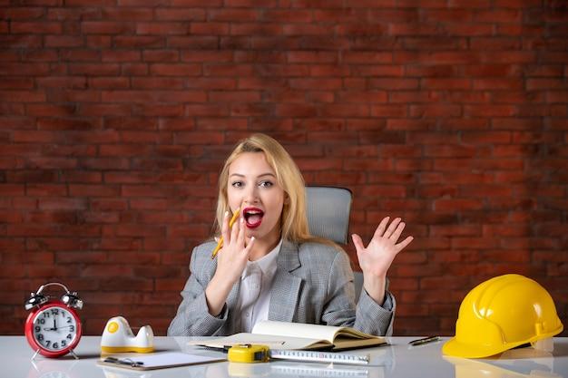 Widok z przodu pozowanie żeński inżynier siedzi za swoim miejscem pracy