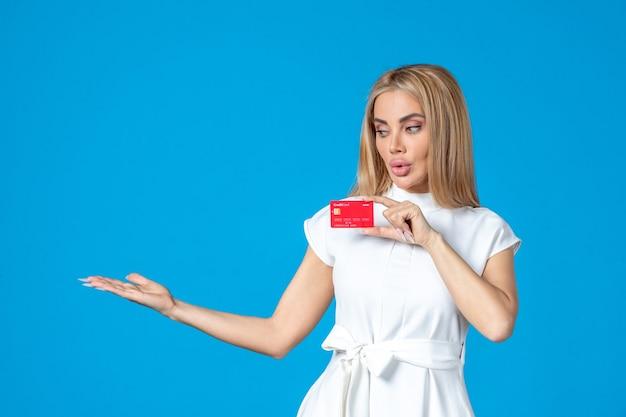 Widok z przodu pracownic trzymającej czerwoną kartę bankową na niebieskiej ścianie