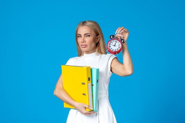 Widok z przodu pracownic trzymającej folder i zegar na niebieskiej ścianie
