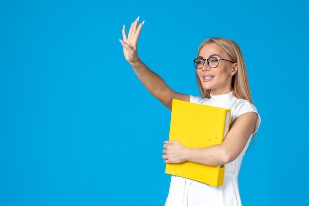Widok z przodu pracownic w białej sukni trzymającej folder i machającej na niebieskiej ścianie