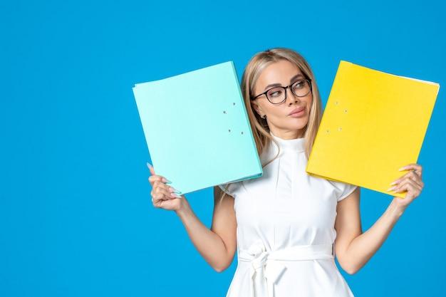 Widok z przodu pracownic w białej sukni trzymającej inny folder na niebieskiej ścianie