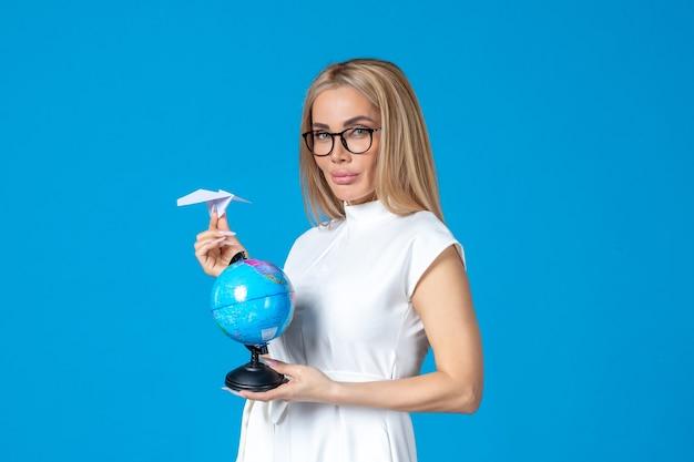 Widok z przodu pracownic w białej sukni trzymającej małą kulę ziemską na niebieskiej ścianie