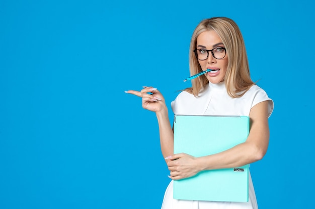 Widok z przodu pracownic w białej sukni trzymającej niebieski folder na niebieskiej ścianie