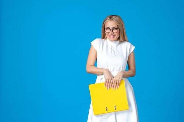Widok z przodu pracownic w białej sukni trzymającej żółtą teczkę i śmiejącej się na niebieskiej ścianie