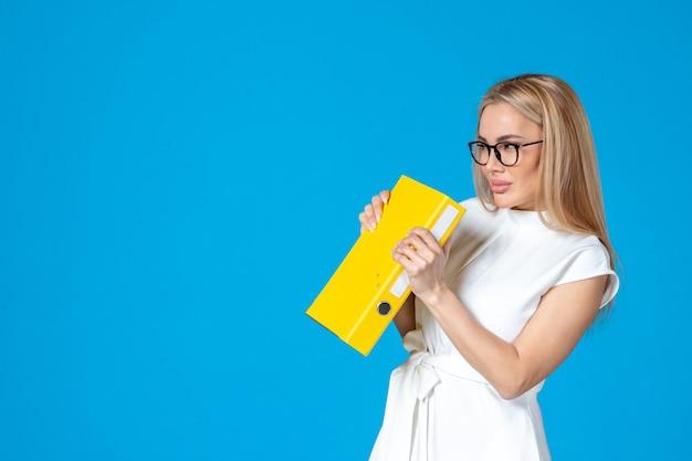 Widok z przodu pracownic w białej sukni trzymającej żółtą teczkę na niebieskiej ścianie