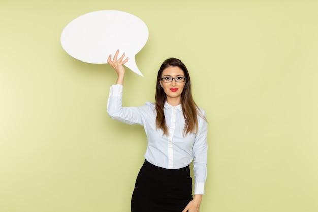 Widok z przodu pracownica biurowa w białej koszuli i czarnej spódnicy, trzymając biały znak na zielonej ścianie
