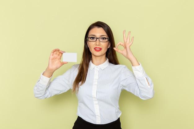 Widok z przodu pracownica biurowa w białej koszuli i czarnej spódnicy trzymającej białą plastikową kartę na jasnozielonej ścianie