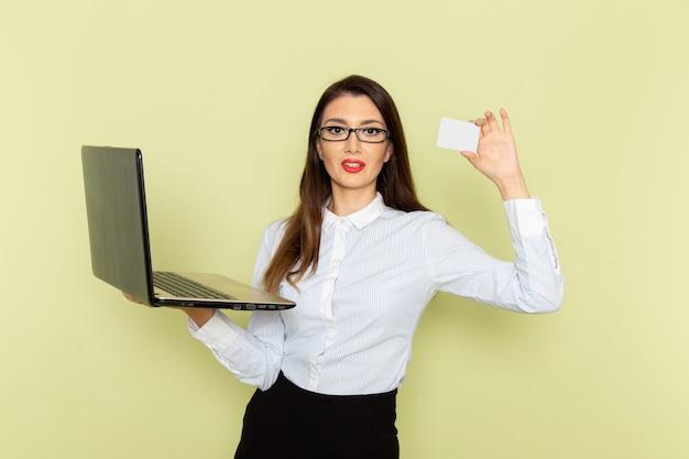 Widok z przodu pracownica biurowa w białej koszuli i czarnej spódnicy za pomocą laptopa i trzymając kartę na jasnozielonej ścianie