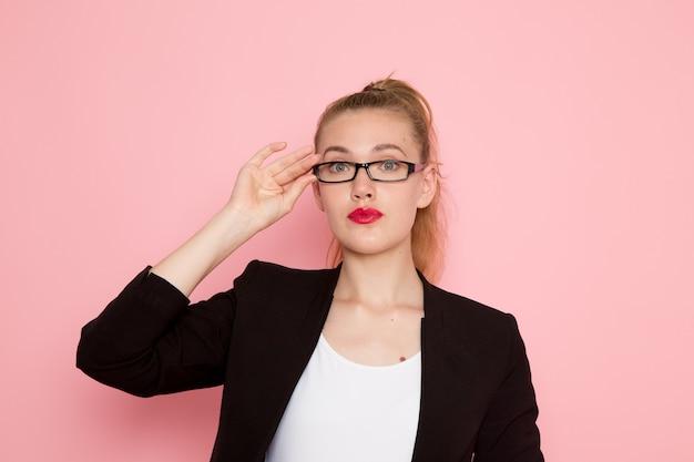 Widok z przodu pracownica biurowa w czarnej surowej kurtce na sobie optyczne okulary przeciwsłoneczne na różowej ścianie
