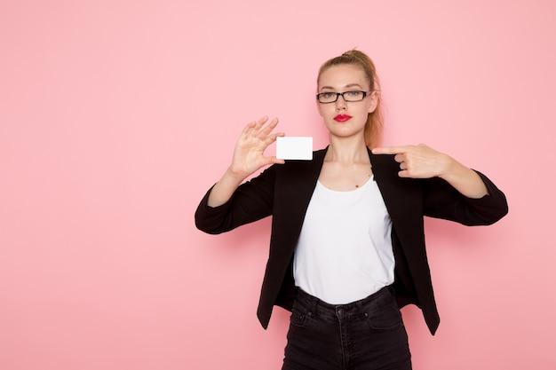 Widok z przodu pracownica biurowa w czarnej surowej kurtce trzyma kartę na jasnoróżowej ścianie