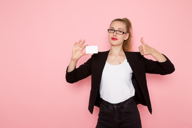 Widok z przodu pracownica biurowa w czarnej surowej kurtce, trzymając białą kartę uśmiechając się na jasnoróżowej ścianie