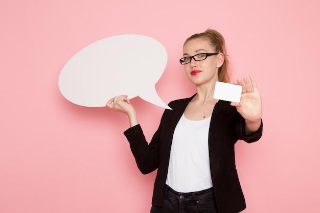 Widok z przodu pracownica biurowa w czarnej surowej kurtce, trzymając biały znak i kartę na różowej ścianie