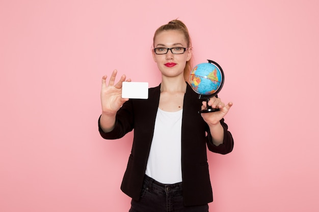 Widok z przodu pracownica biurowa w czarnej surowej kurtce uśmiechnięta trzymając kulę ziemską i kartę na jasnoróżowej ścianie