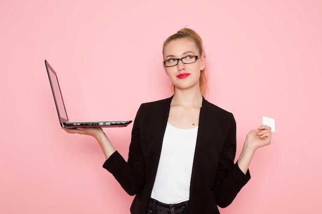 Widok z przodu pracownica biurowa w czarnej surowej kurtce za pomocą swojego laptopa, trzymając kartę na różowej ścianie