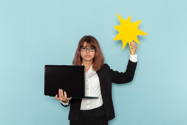 Widok z przodu pracownica biurowa w ścisłym garniturze za pomocą laptopa i trzymając żółty znak na niebieskiej powierzchni