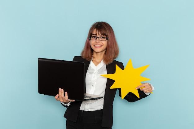 Widok z przodu pracownica biurowa w ścisłym garniturze za pomocą laptopa trzymając żółty znak na jasnoniebieskiej powierzchni