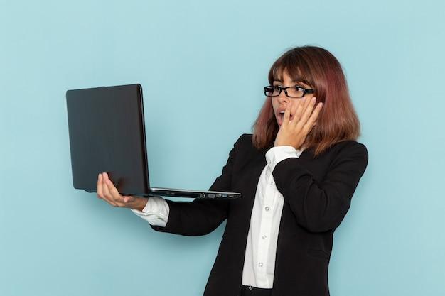 Widok z przodu pracownica biurowa w ścisłym garniturze za pomocą laptopa z zszokowanym wyrazem twarzy na jasnoniebieskiej powierzchni