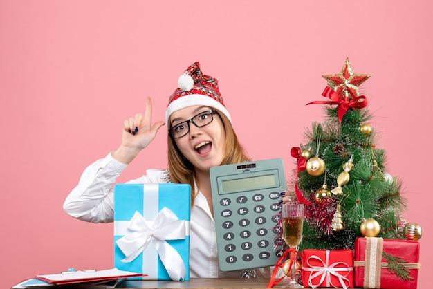 Widok z przodu pracownica gospodarstwa kalkulator wokół przedstawia na różowo