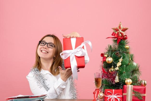 Widok z przodu pracownica siedząca wokół prezentów świątecznych i drzewa na różowo